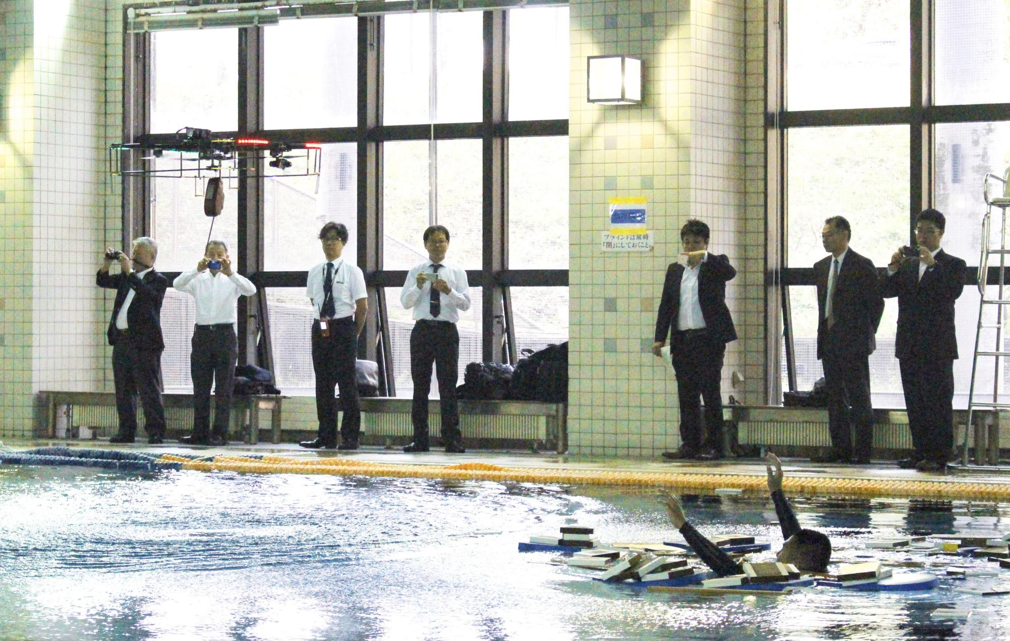 A water rescue drill using a drone is conducted at a swimming pool of the Tokyo Fire Department's fire academy in October 2016. | KYODO
