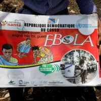 A Congolese volunteer displays a flip book he uses to inform people about the Ebola virus, in Goma, Congo, on Saturday. A woman in her 70s from Saitama Prefecture who recently returned from a visit to Congo has tested negative for a possible Ebola infection at a medical institute in Tokyo, the health ministry said Sunday. | REUTERS