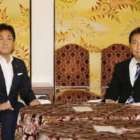 Yukio Edano (right), head of the Constitutional Democratic Party of Japan, and Democratic Party for the People chief Yuichiro Tamaki hold talks Monday in the Diet over the possible formation of a joint parliamentary group in the Lower House to counter the ruling bloc. | KYODO