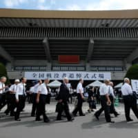 People arrive for a memorial ceremony for the war dead at Nippon Budokan Hall, adjoining the Imperial Palace in Tokyo, on Thursday as Japan marks the 74th anniversary of its surrender in World War II. | AFP-JIJI