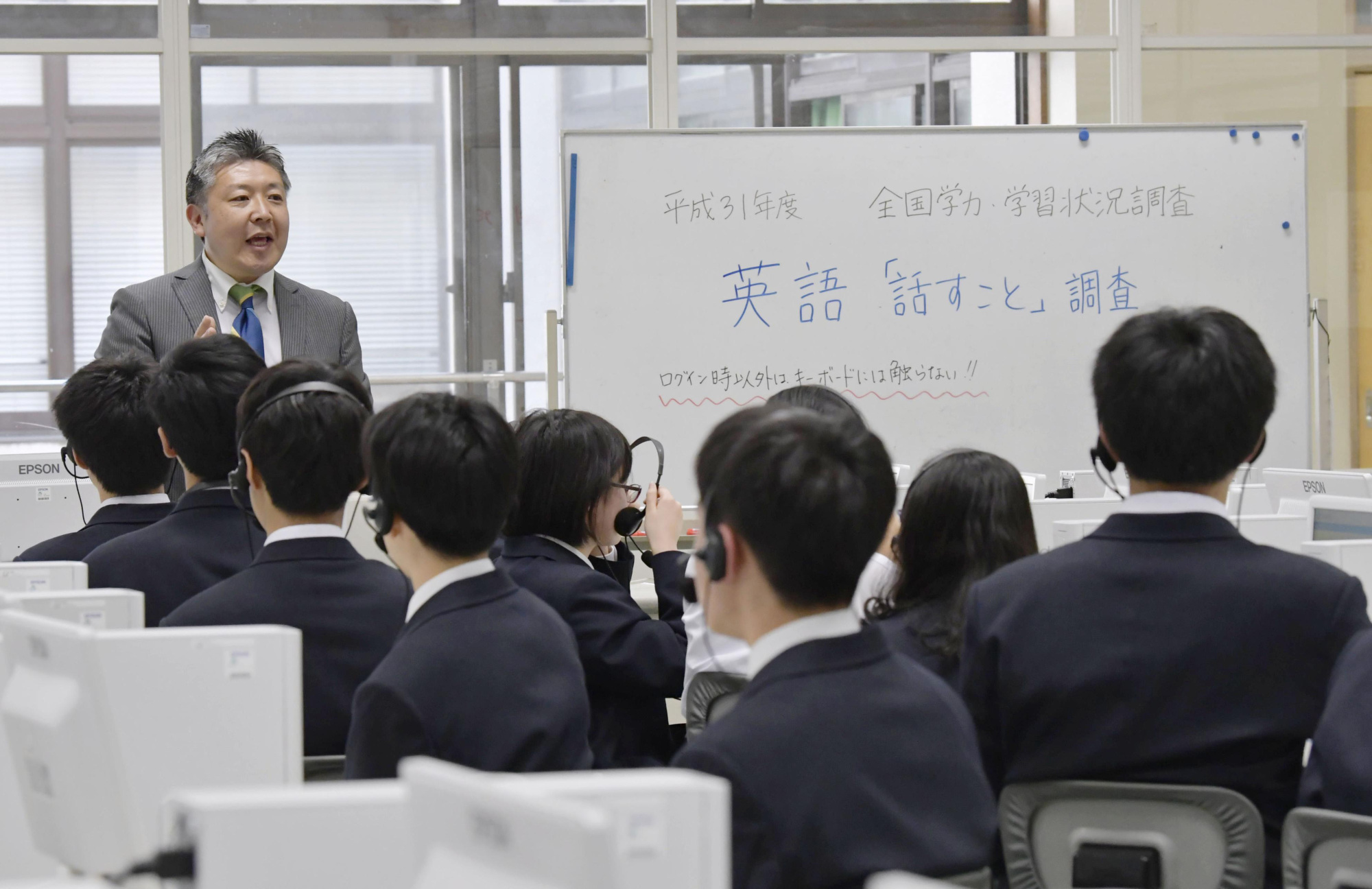 Students at a junior high school in Tokyo take the speaking portion of this year's nationwide English achievement test in April. | KYODO