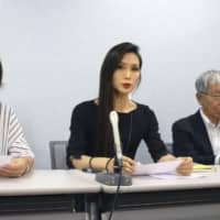 A lawyer (center) representing a woman who sued her employer over gender issues speaks at a news conference in Osaka on Friday. | KYODO