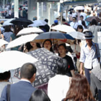 Pedestrians use parasols to shield themselves from the hot sun in Tokyo's Ginza district on Wednesday. | KYODO