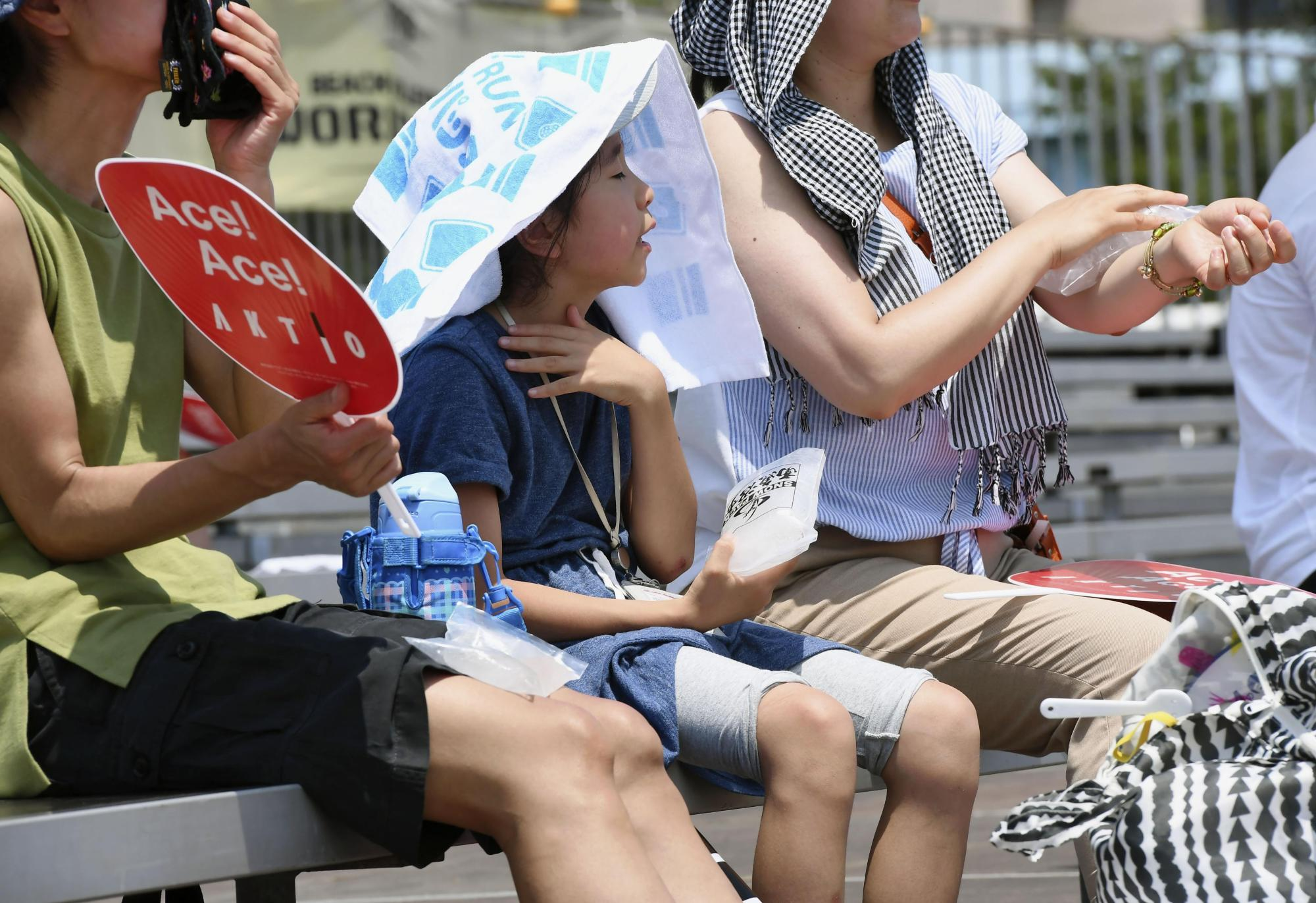People find ways to cool down during a beach volleyball test match for the upcoming Olympics held in Tokyo on July 24.   KYODO