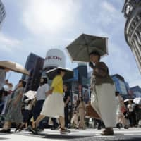 Parasols help pedestrians beat the heat in the Ginza district of Tokyo on Aug. 7. | KYODO