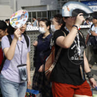 People hold fans to block out the sun in Tokyo's Koto Ward on Sunday. | KYODO