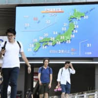 People walk below a large screen in Tokyo's Akiharaba district on Saturday that shows temperatures were forecast to rise above 30 C across the nation that day. | KYODO