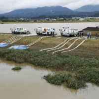 Officials work to drain water in Omachi, Saga Prefecture, on Thursday after torrential rain caused flooding in many areas. | KYODO