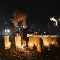 People light paper lanterns with various messages to pay tribute to the victims of the landslides in Hiroshima on Tuesday, the fifth anniversary of the disaster. | KYODO