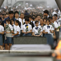 People bring flowers to lay at the cenotaph in Hiroshima's Peace Memorial Park on Tuesday. A ceremony was held to mark the 74th anniversary of the atomic bombing. | KYODO