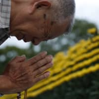 A man prays at the cenotaph at the Peace Memorial Park in Hiroshima on Tuesday, the 74th anniversary of the U.S. atomic bombing. | KYODO