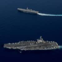 The USS Ronald Reagan aircraft carrier sails in the foreground as the Maritime Self-Defense Force's Izumo helicopter carrier steams into formation during a combined MSDF and U.S. Navy exercise on June 15, 2017, in the South China Sea. | U.S. NAVY