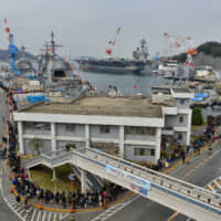 Visitors wait in line for a tour of the USS Chancellorsville destroyer during the 26th annual Spring Festival at the U.S. naval base in Yokosuka, Kanagawa Prefecture, on March 30. Beijing appears to have been practicing for pre-emptive missile strikes on forward bases that underpin U.S. military power in the western Pacific, including the Yokosuka base. | U.S. NAVY