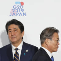 South Korean President Moon Jae-in walks past Prime Minister Shinzo Abe prior to a group photo session at the Group of 20 summit in Osaka in June. | BLOOMBERG