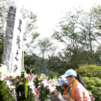People pray for the victims of the 1985 Japan Airlines jumbo jet crash at Osutaka Ridge in Gunma Prefecture on Monday. | KYODO