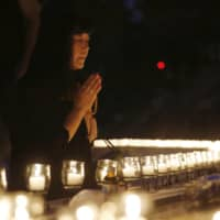 A woman prays Monday among lighted candles in the village of Ueno, Gunma Prefecture, as she remembers those who died in the August 1985 crash of a Japan Airlines jumbo jet. | KYODO