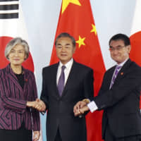 Chinese Foreign Minister Wang Yi (center) holds the hands of South Korean counterpart Kang Kyung-wha (left) and Japanese counterpart Taro Kono on Wednesday ahead of their meeting in Beijing. | AP