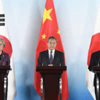 China's Wang Yi urges Japan and South Korea to solve dispute during trilateral talks