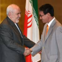 Iranian Foreign Minister Mohammad Javad Zarif shakes hands with Foreign Minister Taro Kono during their meeting at a hotel in Yokohama on Tuesday.  | POOL / VIA AFP-JIJI