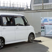A minivehicle equipped with sensors to avoid collisions stops before an obstacle in Osaka. | KYODO