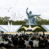 Doves fly around the Peace Statue at the Peace Park in Nagasaki on Friday as a memorial ceremony was held to mark the 74th anniversary of the atomic bombing of the city.   KYODO