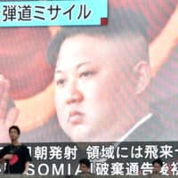 A report on North Korean leader Kim Jong Un overseeing a missile launch Saturday is seen on a giant television screen in Tokyo. | AFP-JIJI
