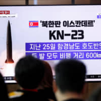 People watch a TV broadcast of a news report in Seoul on North Korea's firing of short-range ballistic missiles, on July 31. | REUTERS