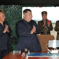 North Korean leader Kim Jong Un celebrates after a successful missile test on Saturday. | REUTERS