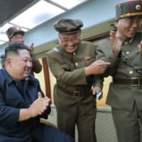 North Korean leader Kim Jong Un celebrates the successful test-firing of a new weapon at an undisclosed location on Friday. | AFP-JIJI