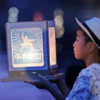 A boy holds a paper lantern in remembrance of victims of the 1945 atomic bombing, in Nagasaki on Friday. | REUTERS