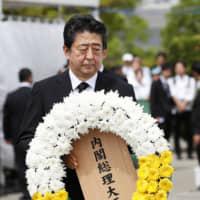 Prime Minister Shinzo Abe offers a flower wreath for the victims of the 1945 atomic bombing of Nagasaki, at the city's Peace Park on Friday. | REUTERS