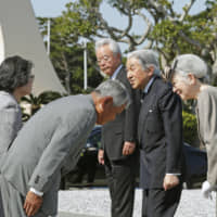 Then-Emperor Akihito and Empress Michiko talk to family members of those who lost their lives during World War II, at the Peace Memorial Park in Itoman, Okinawa Prefecture, on March 27, 2018. | KYODO
