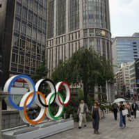 People walk past the Olympic rings in Tokyo last Monday. | AP