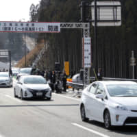 Cars drive on what is known as the 'Reconstruction Road' in the town of Sanriku, Miyagi Prefecture, in February. | KYODO