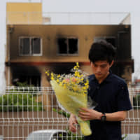 A man carries flowers as he prays for victims in front of the torched Kyoto Animation building in the city on July 20.  | REUTERS