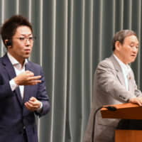 Kohei Ehara, a sign language interpreter, works besides Chief Cabinet Secretary Yoshihide Suga during a news conference at the Prime Minister's Office in Tokyo on June 20. | SATOKO KAWASAKI