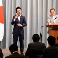 Kohei Ehara, a sign language interpreter, works beside Chief Cabinet Secretary Yoshihide Suga during a news conference at the Prime Minister's Office in Tokyo on June 20. | SATOKO KAWASAKI