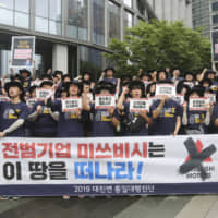 South Korean college students shout slogans during a rally to denounce Japan's new export controls on South Korea in front of the office of Mitsubishi Corp. in Seoul on Wednesday. | AP