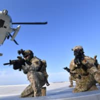 Members of the South Korean Navy's special forces deploy from a UH-60 helicopter during a military drill Sunday on the islets called Takeshima in Japan and Dokdo in South Korea. | AP