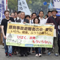 Plaintiffs in a lawsuit seeking damages compensation over the 2011 Fukushima nuclear power plant meltdown crisis walk toward the Tokyo District Court on Aug. 2. | KYODO
