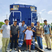 Train enthusiasts pose for a picture on a DD51-class diesel locomotive in Thailand. | KYODO