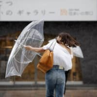 A woman is caught in strong wind and rain on Tuesday morning in the city of Fukuoka after Typhoon Francisco made landfall on Kyushu. | KYODO