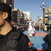 Women perform a traditional dance in the main bazaar of Urumqi, in China's Xinjiang autonomous region, as a security guard stands by in November 2018. | BLOOMBERG