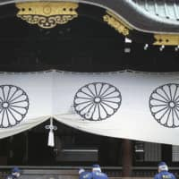 Police investigate the Yasukuni Shrine on Monday after a man threw a black liquid onto a white curtain and was arrested for property damage. | KYODO