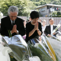 Somber occasion: Kaoru Irikura (right), head of Tsukuri Yamayuri-en, prays in front of an altar set up near the facility on the third anniversary of a stabbing rampage that targeted people with mental disabilities. | KYODO