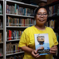 A wall of words: Tin Tin Win, a pro-democracy activist who came to Japan in 1991 and started a library in 2000, holds one of the newer books that has been added to the library's collection. | KYODO