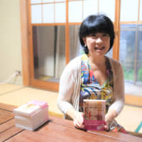 Writer Mitsuyo Okada holds up a copy of her latest book 'The Never-ending Spell of New York.' | KYODO