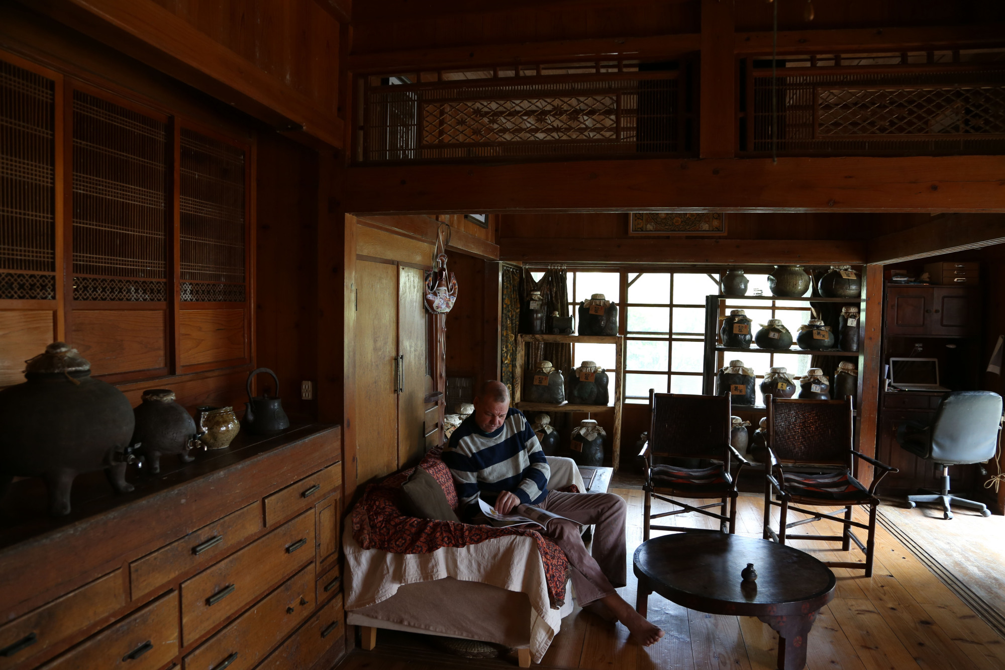 Paul Lorimer relaxes in the remodeled living room of his traditional Okinawan-style home. Awamori jars of all sizes fill shelves as well as the alcove area, waiting for their time to ripen. The largest of the jars hold nearly 90 liters, and even the middle-sized jars hold 36. 'If they're too small, the clay ultimately overpowers the liquor and puts the flavor off balance,' he says. He also warns, 'When you buy a new jar, the most important first step is a deep cleaning to get rid of any harsh residues left from the firing.' The suggested process is onerous enough that Sakiyama Shuzo offers a service to take care of it for those who are interested. | KENGO TARUMI