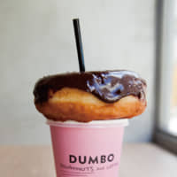 Stack 'em: Dumbo Doughnuts and Coffee's salted chocolate caramel doughnut fits perfectly on top of its pastel-pink coffee cups. | COURTESY OF INCEPTION INC.