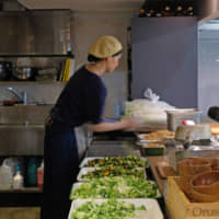 Food for a crowd: Staff at Tiny Peace Kitchen prep hefty bowls of that day's side dishes before lunch service.   CLAIRE WILLIAMSON